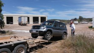 Ray watches his vehicle being loaded on a trailer at Owieandana